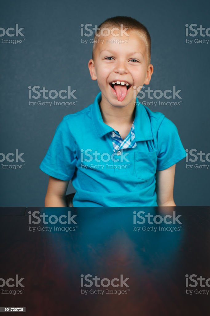 Silly boy sticking tongue out at desk royalty-free stock photo