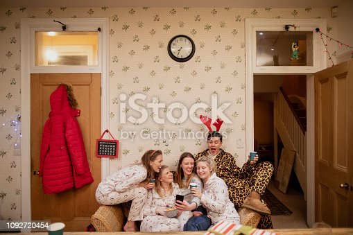 Small group of young adults are sitting on a sofa in a dining room at a Christmas house party. They are taking selfies on smart phones while wearing pyjamas and novelty accessories.