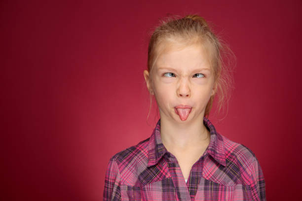silly face young girl in purple shirt looking straight at camera stock photo