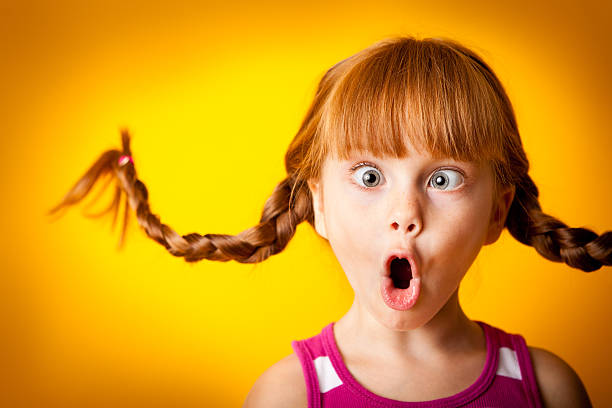 Silly, Red-Haired Girl with Upward Braids Making Crazy Face stock photo