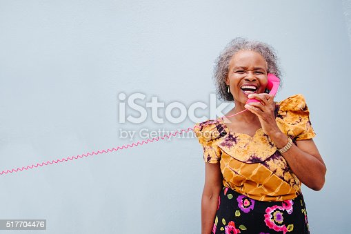 Senior  woman having fun with pink wintage telephone, isolated on blue wall background
