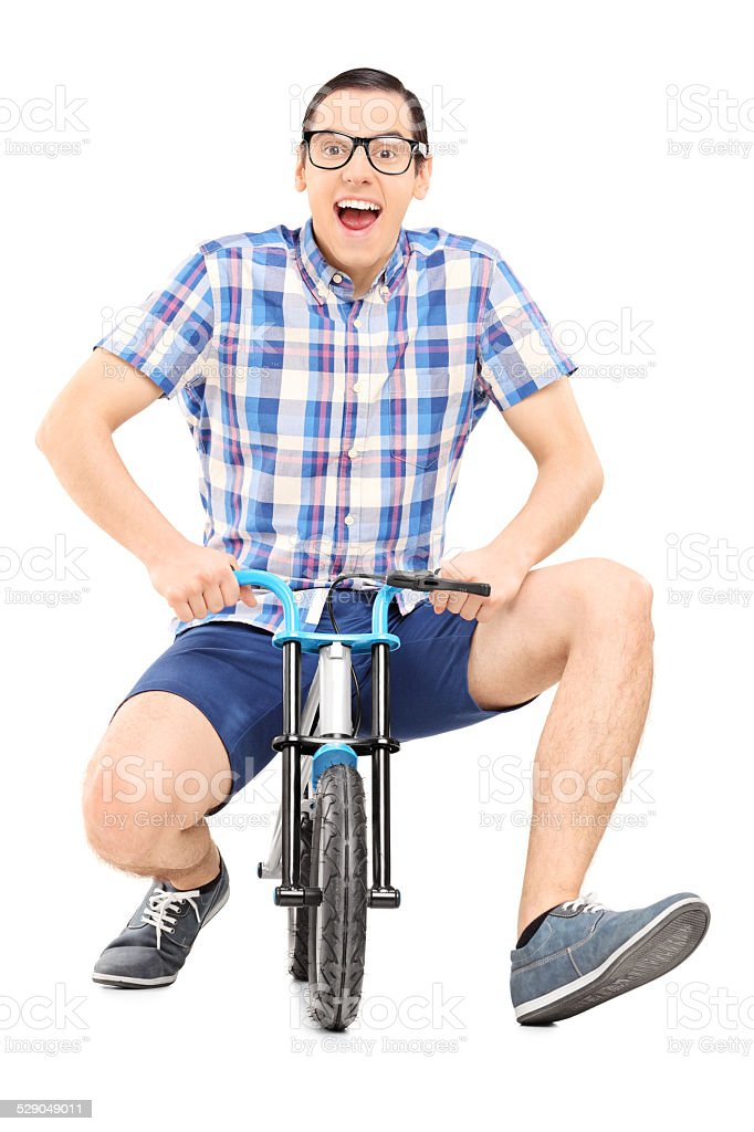 Silly young man riding a small childish bike stock photo