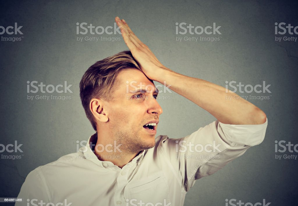 silly young man, slapping hand on head stock photo