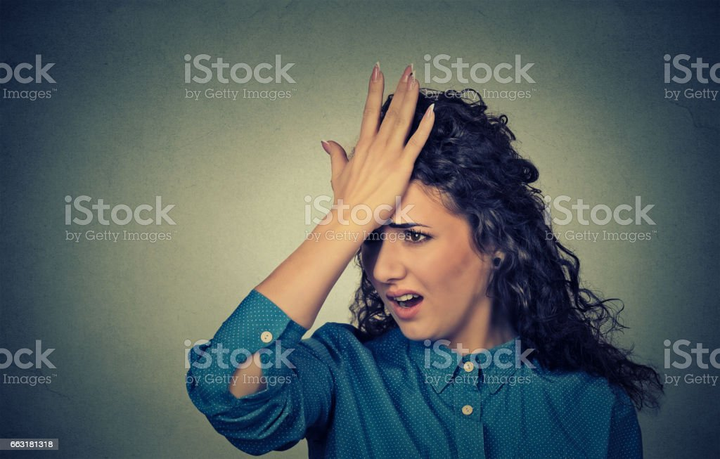 silly young woman, slapping hand on head having duh moment stock photo