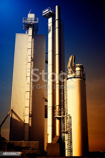 Silo and exhaust pipes - toned image, back lit