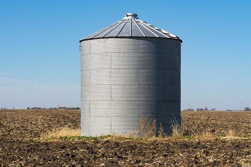 Metal silo in open field.