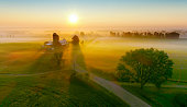 Silos and trees cast long shadows in fog at sunrise, scenic rural landscape, aerial view.
