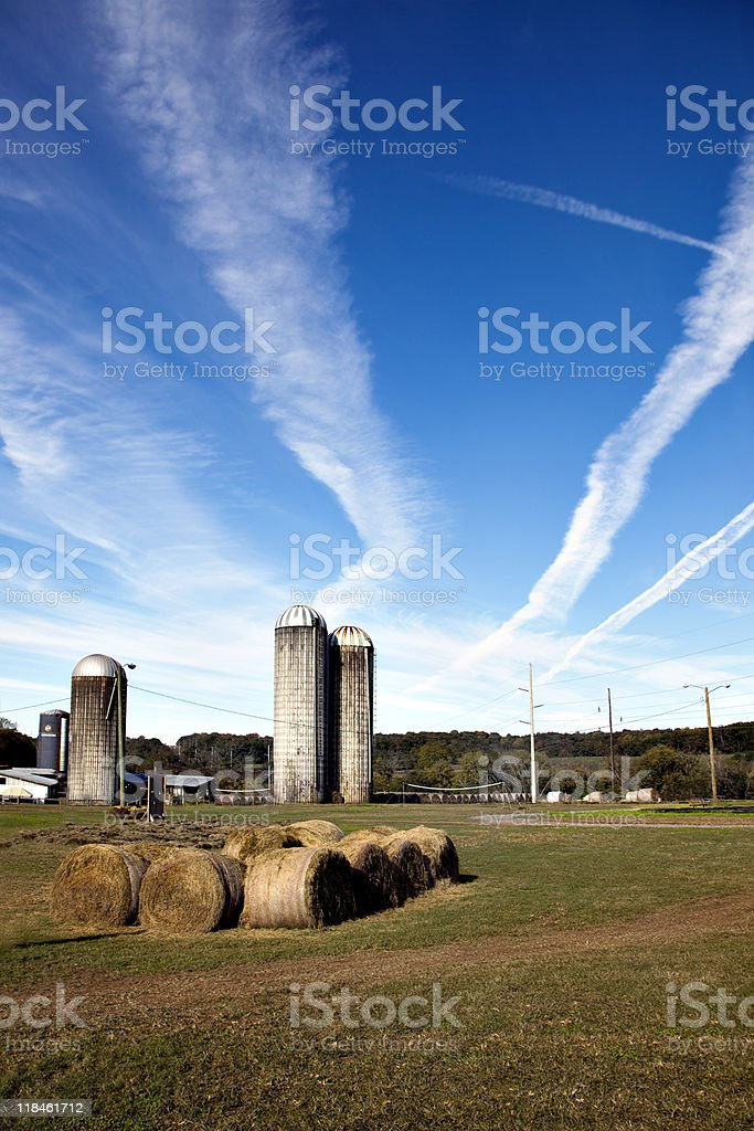 Silos with blue sky and jet contrails royalty-free stock photo