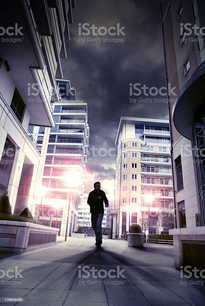 Silouette of man running through city street stock photo