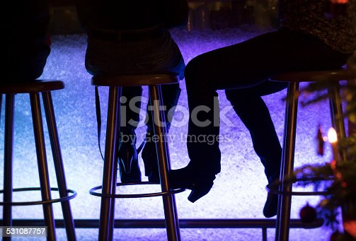 istock Silouette of people at the bar against violett bar light 531087757