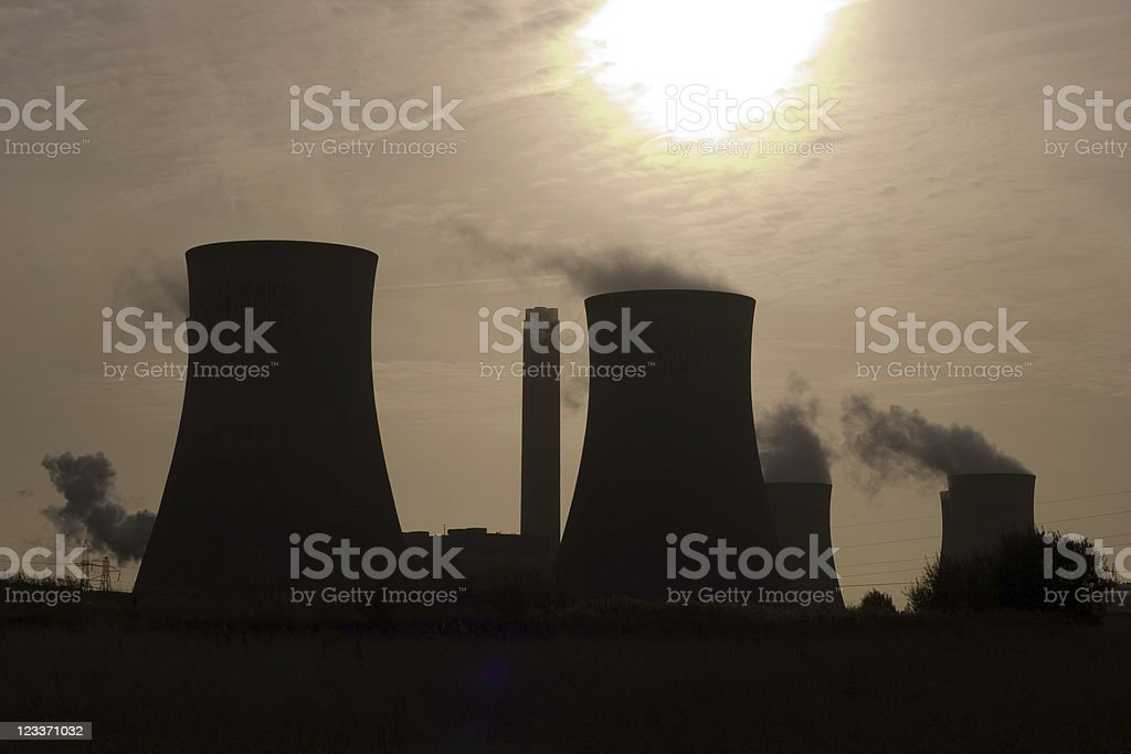 silouettes of coal power station cooling towers stock photo