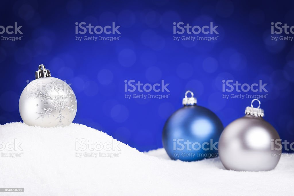 Silver and blue Christmas baubles on snow, blue background royalty-free stock photo