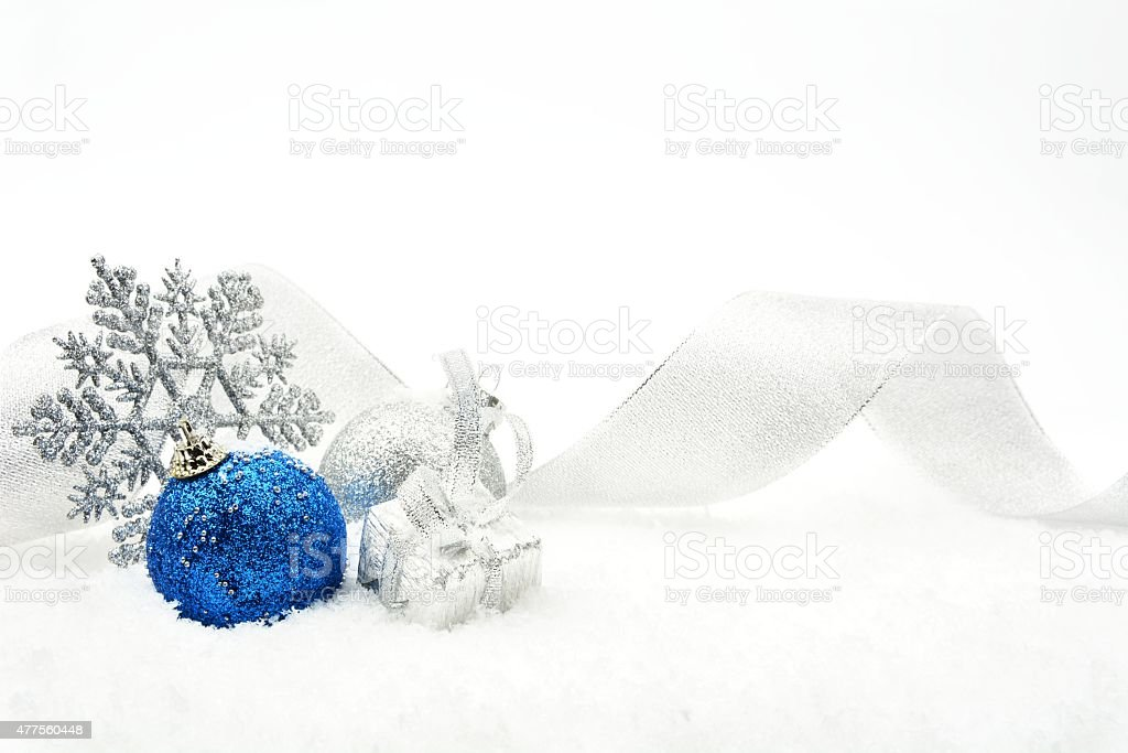 Silver and blue christmas glittering baubles with ribbon on snow stock photo