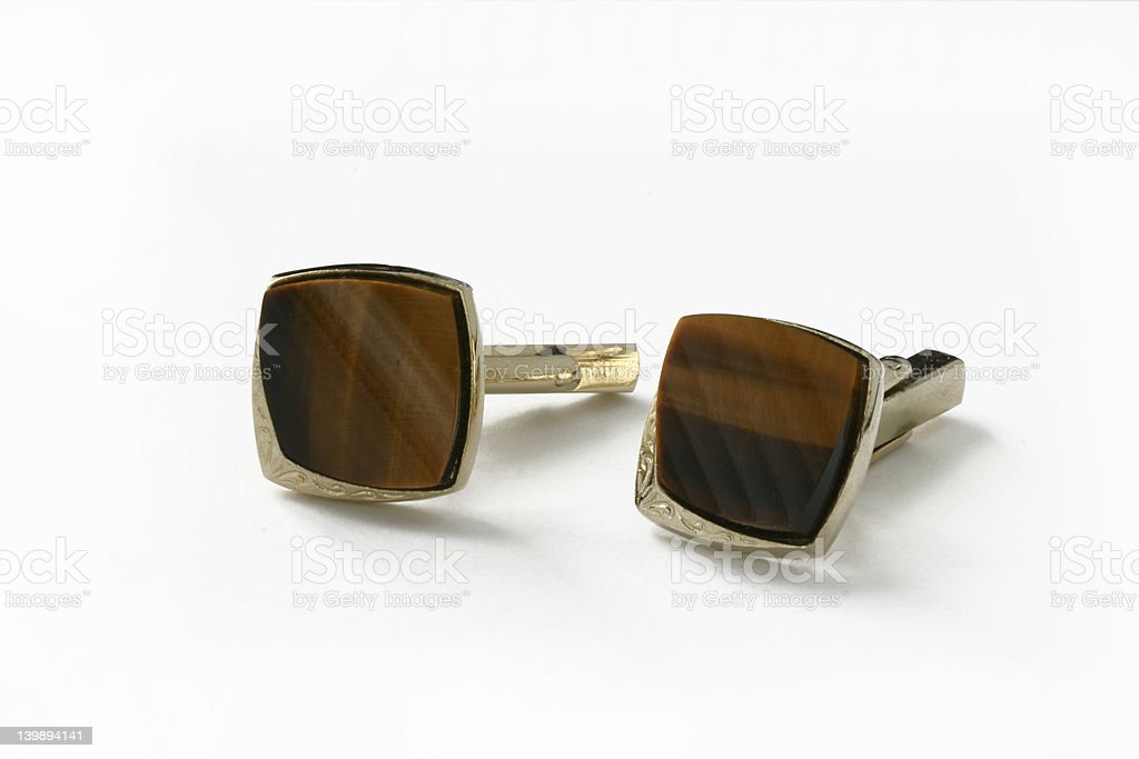 Silver and brown cufflinks on white background stock photo
