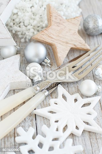 istock Silver and cream fork and knife  with christmas decorations 607920990