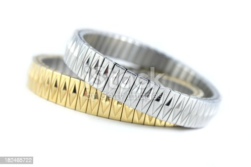 A pair of silver and gold bracelets isolated on a white background.