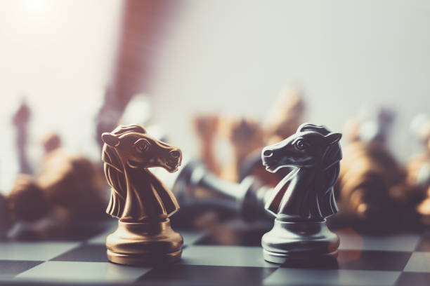 silver and gold horse chess on board - battle stock photos and pictures