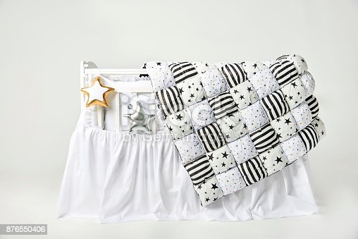istock Silver and gold star shaped pillows and patchwork comforter on a white baby cot 876550406
