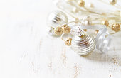 Silver and golden Christmas ornaments on a white wooden background
