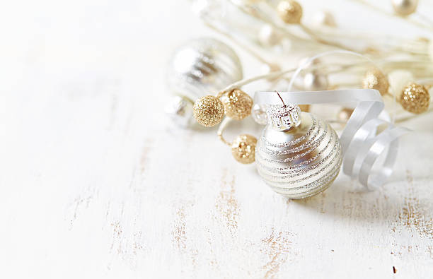 silver and golden christmas ornaments on a white wooden background - vintage ornaments stock photos and pictures