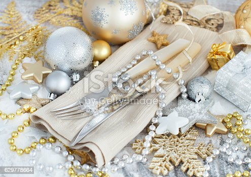609031028 istock photo Silver and golden Christmas Table Setting 629778664