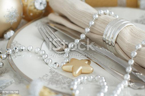 609031028 istock photo Silver and golden Christmas Table Setting 629778736
