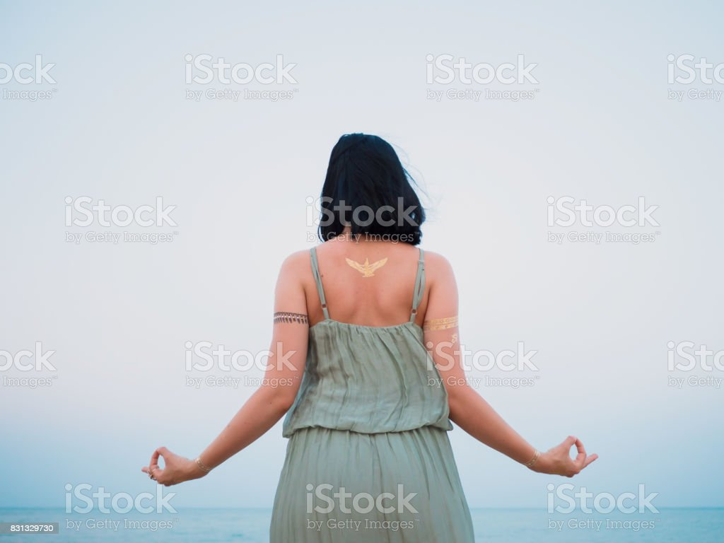 Silver and golden flash tattoo on female hands over sea or ocean background. Woman practicing yoga. Gyan Mudra stock photo