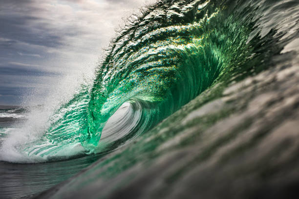 Silver and green wave breaking in the ocean stock photo
