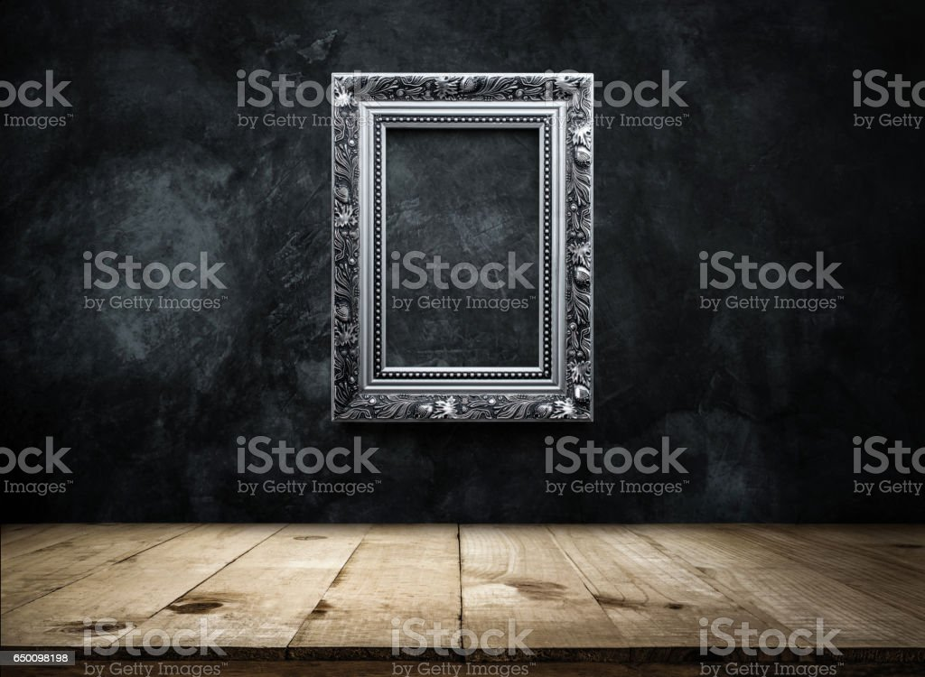 silver Antique picture Frame on dark grunge wall with Wooden table top, Empty ready for product display or montage. stock photo