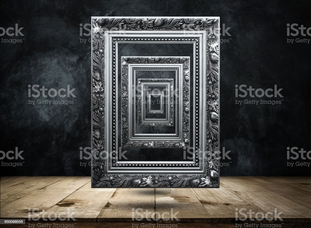 silver Antique picture Frame on dark grunge wall with Wooden table top mysterious, confused, background concept. stock photo