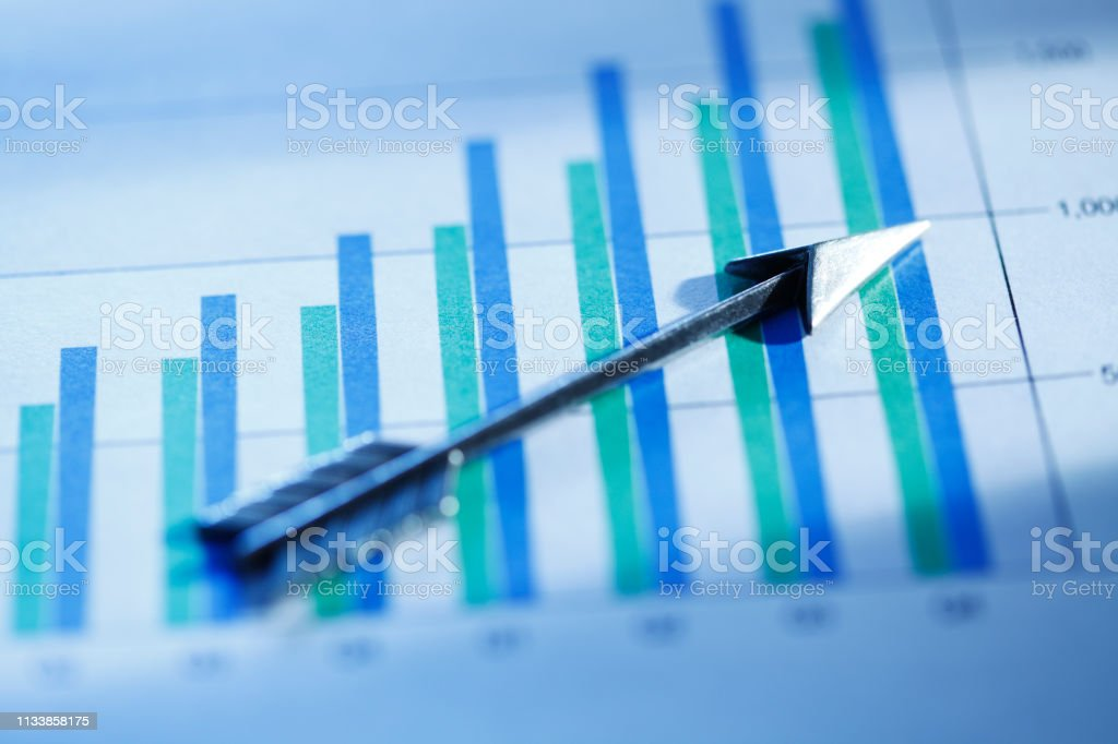 Silver Arrow Resting On Chart stock photo