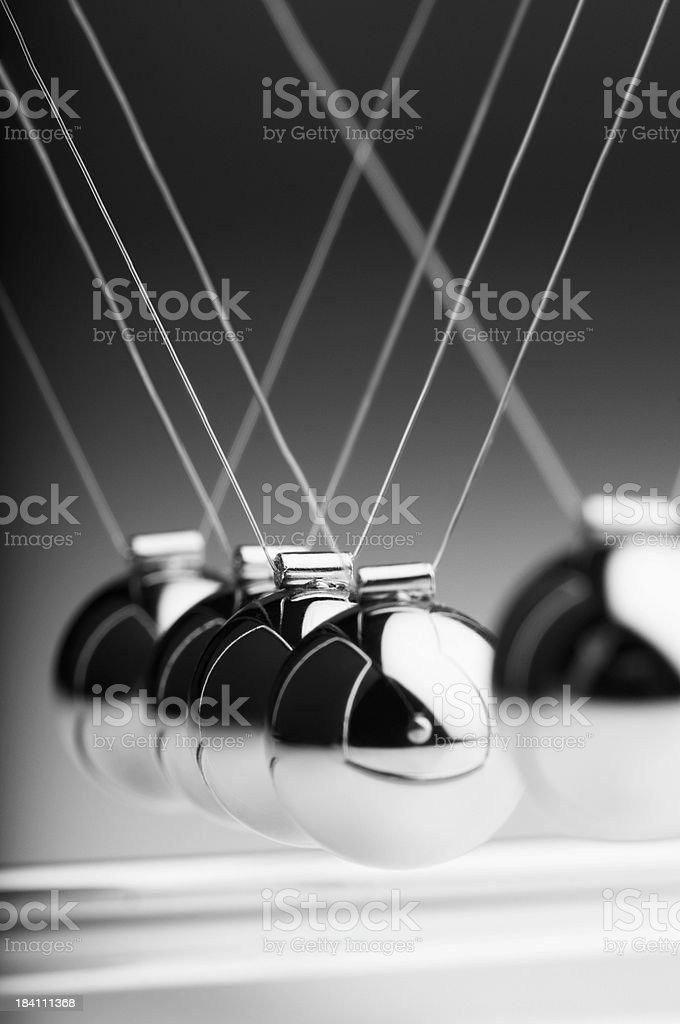 1 silver ball in Newton's cradle swings back toward others stock photo
