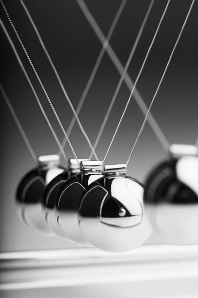 1 silver ball in newton's cradle swings back toward others - pendulum stock photos and pictures