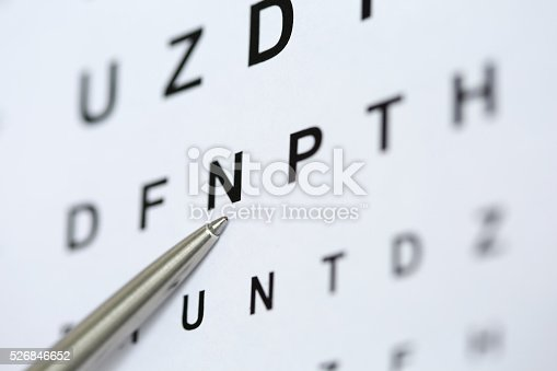 istock Silver ballpoint pen pointing to letter in eyesight check table 526846652