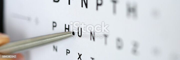 istock Silver ballpoint pen pointing to letter in eyesight check table 586080342