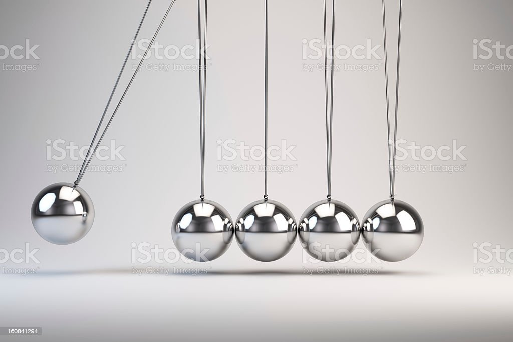 Silver balls of Newton's cradle swing back and forth royalty-free stock photo