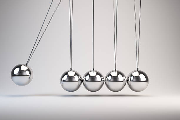 silver balls of newton's cradle swing back and forth - pendulum stock photos and pictures