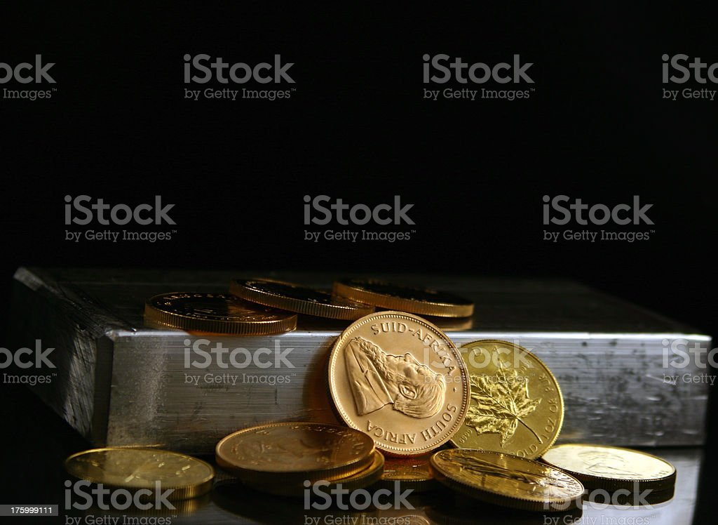 Silver bar, Gold coins on black. royalty-free stock photo