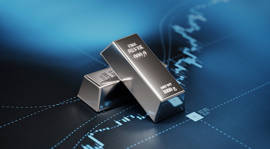 Silver bars sitting on blue graph. Selective focus. Horizontal composition with copy space. Stock market and finance concept.