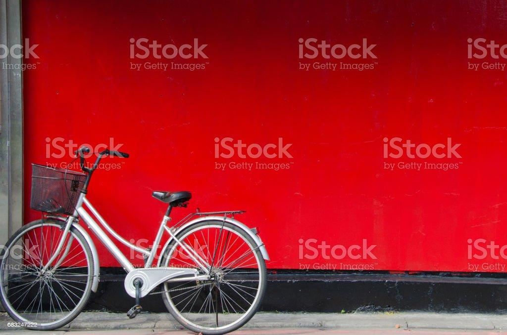 銀自行車的停放在紅牆前。 免版稅 stock photo