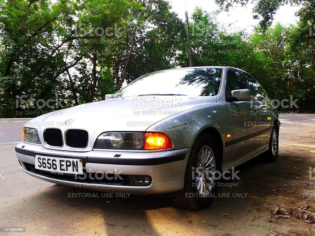 Silver BMW 528i SE on the roadside stock photo