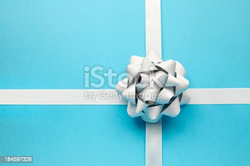 A silver bow on a blue striped background.