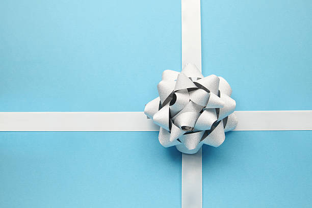 silver bow on blue - wrapping paper stock photos and pictures