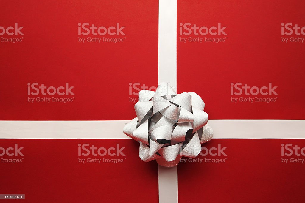 Silver bow on red stock photo