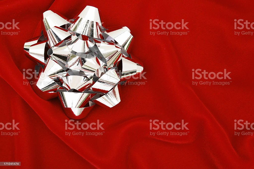 Silver bow on red velvet royalty-free stock photo