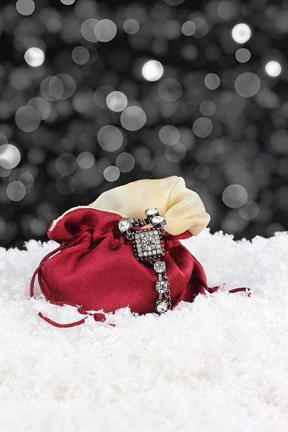 Silver bracelet draped on red satin pouch in snow stock photo