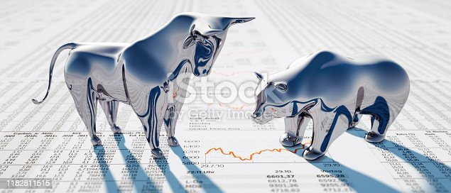 Silver Bull and Bear standing on a financial Newspaper with Charts
