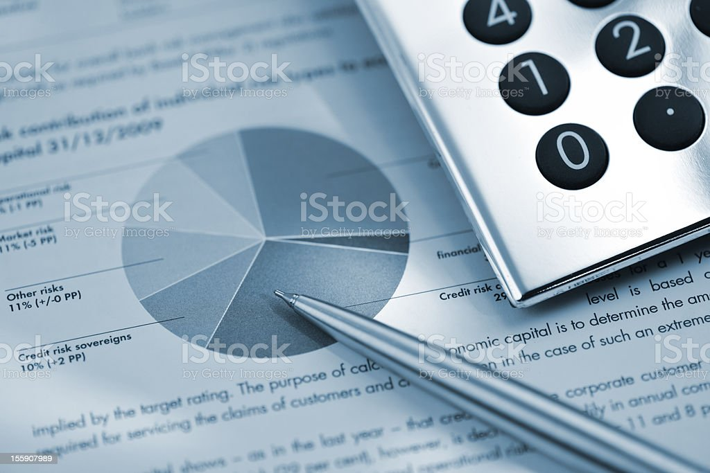 silver calculator and pen on sheet of financial data stock photo