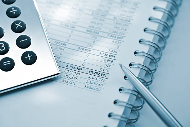 silver calculator and pen on sheet of financial data  accounting ledger stock pictures, royalty-free photos & images