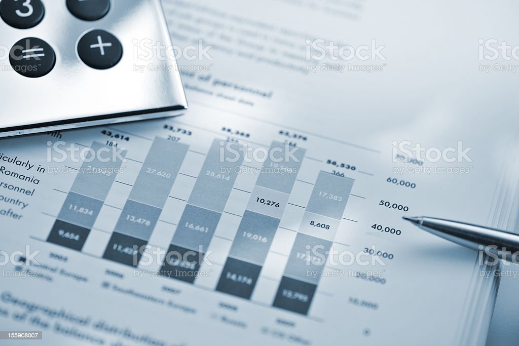 silver calculator and pen on sheet of financial data royalty-free stock photo